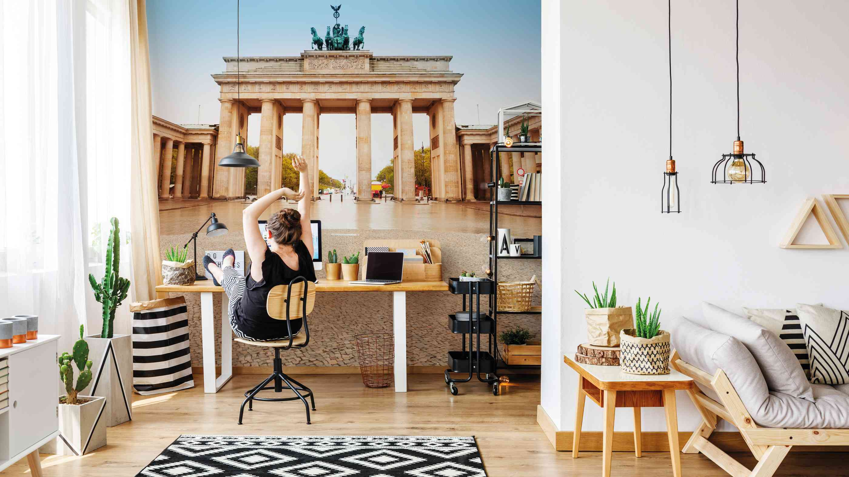 Young creative artist working at desk in her cozy apartment in natural botanic style with plants, black storage cart, wooden floor and trendy hipster decorations